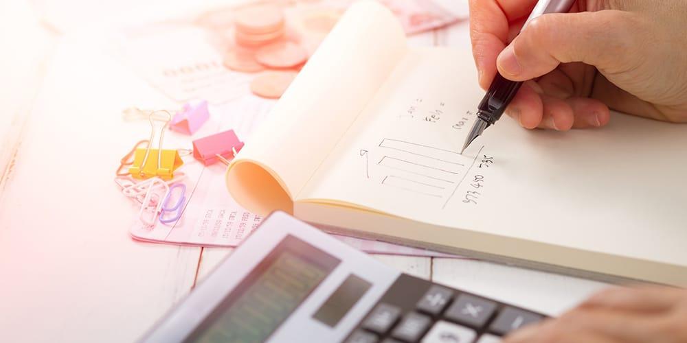 Calculatrice au premier plan et main tenant un stylo au dessus d'un calepin