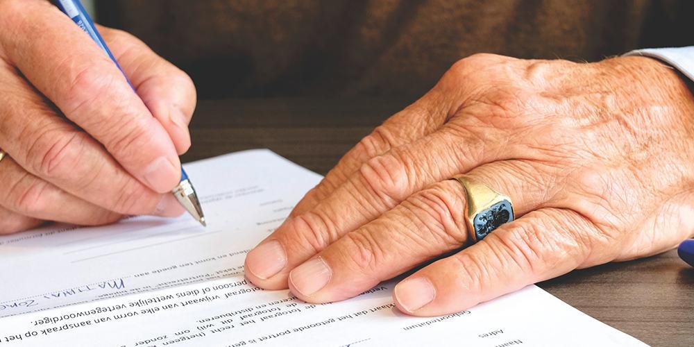 Mains de personnes âgée signant un contrat