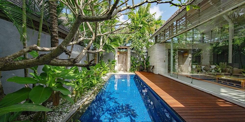 Villa avec petit jardin au bord d'une longue piscine creusée