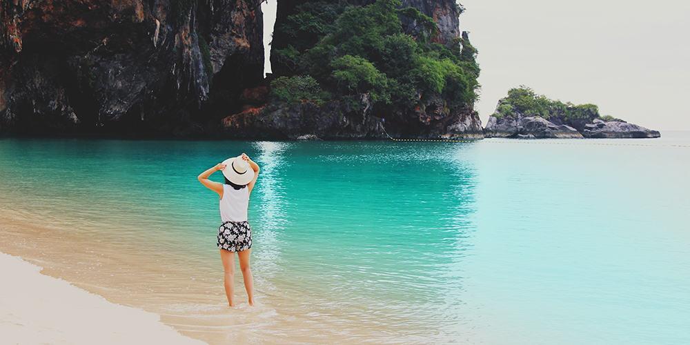 Jeune femme de dos sur une plage, les pieds dans l'eau